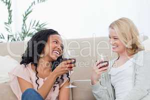Two women sitting on the floor are talking and drinking wine