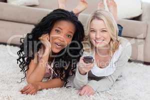 Two women are smiling at the camera and lying on the ground