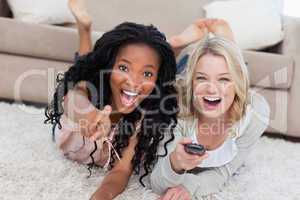 Two laughing women are lying on the ground and looking at the ca