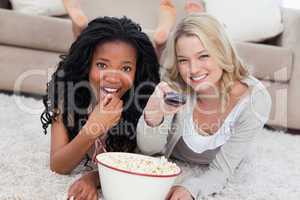Two women lying on the ground with a bowl of popcorn