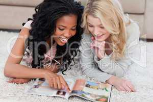 A woman is pointing at a magazine with her friend beside her