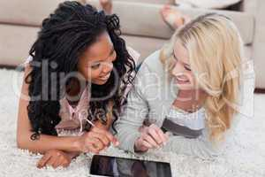 Two women lying down are looking at each other with a tablet in