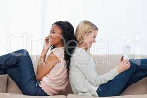 Two women sitting back to back on a couch