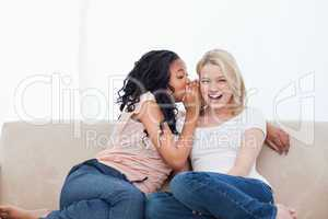 A woman sitting on a couch is whispering into her friends ear