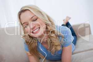A woman lying on a couch is listening to music with earphones