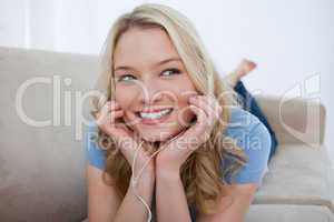 A smiling woman is listening to music with her earphones