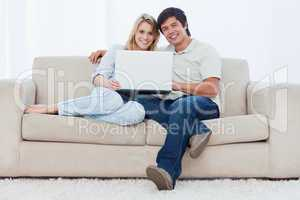 A smiling couple with a laptop are looking at the camera