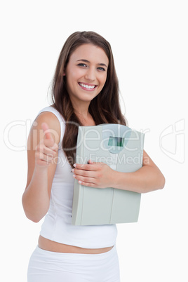 Smiling brunette putting her thumbs up while holding weighing sc