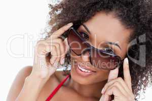 Smiling woman looking aver her sunglasses