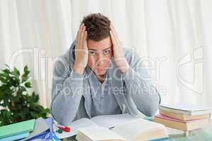 Portrait of a distressed student doing his homeworks
