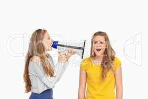 Female student using a loudspeaker on a other girl