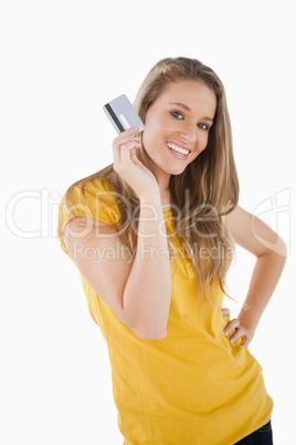 Portrait of a blonde student showing a credit card