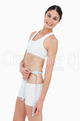 Slim brunette measuring her waist