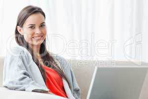 Half length shot of a smiling woman on the couch looking into th