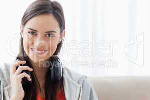 A brightly smiling woman holding headphones as she looks into th