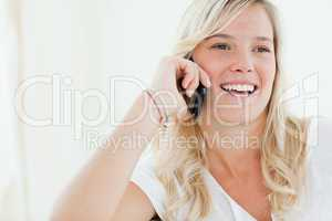 Close up of a woman laughing on her phone as she looks to the si