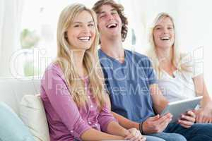 Laughing group of friends sitting as they use a tablet