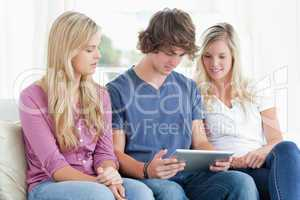 Three people pay attention to the tablet in front of them
