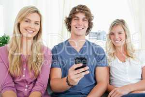 Three friends looking at the camera as the boy has a phone in hi
