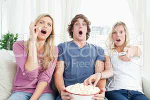 Three friends enjoying popcorn together while shocked at the tv