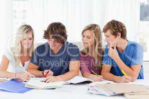 Four students sitting together and trying to get the answer