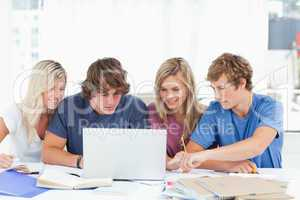 A group of students use a laptop to answer their questions