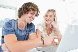 A smiling couple looking at the laptop with the woman looking at
