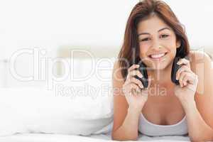 Woman on the bed listening to music on her earphones and smiling