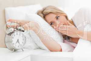 Woman waking up, yawning nd reaching over to silence alarm clock