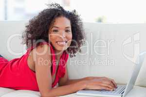 Woman lying forward on a couch with her laptop in front of her