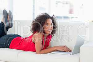 Woman with raised legs on the couch smiling and using her laptop