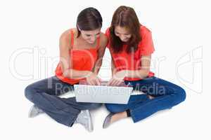 Two cute teenagers sitting cross-legged while looking at a lapto