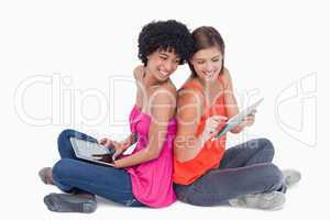 Smiling teenage proudly showing her tablet PC to her friend