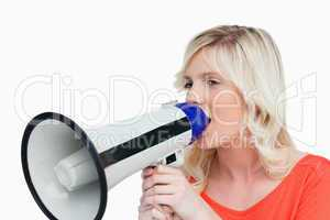 Young woman looking on the side while speaking into a megaphone