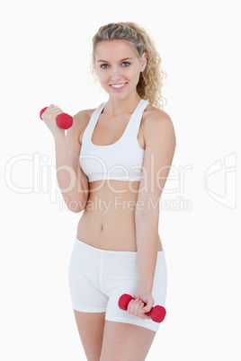 Smiling teenager in sportswear lifting weights