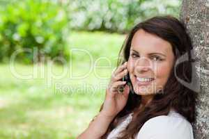 Young smiling woman talking on the phone while looking at the ca