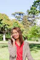 Woman smiling while making a phone call in and area surrounded b