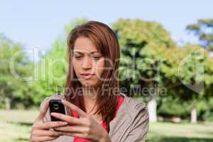 Serious woman reading a text message in a bright grassland area