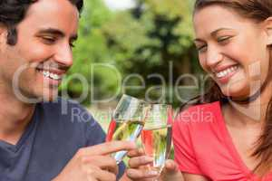 Two friends smiling as they touch glasses of champagne together