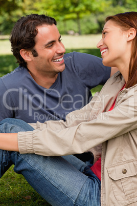 Two friends laughing while they are both sitting on the grass
