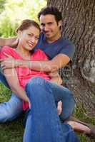 Man looking ahead as he holds her while they sit together in the