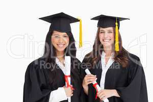 Two friends stand together after graduating