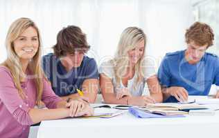 A study group working hard as one girl smiles and looks at the c