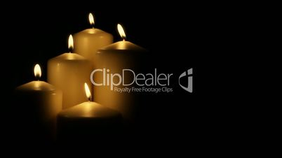 Five flickering candles on the black background