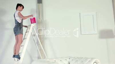 Junge Frau streicht die Wand rot
