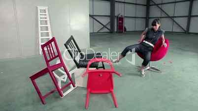 Junge Frau schmeißt Stühle um