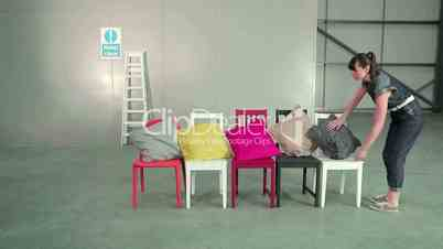 Junge Frau legt Kissen auf Stühle