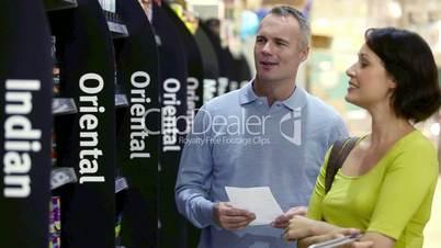 Junges Paar kauft im Supermarkt ein