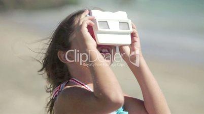 Girl looking through slide viewer on beach