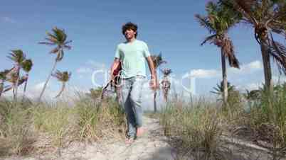 Young man walking with guitar on beach